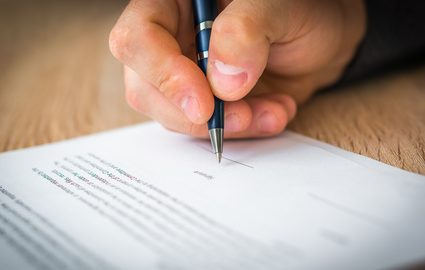 hand signing a sales contract