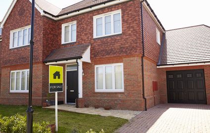 Exterior of detached property house with garage With For Sale Sign In Garden