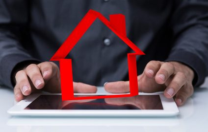 Outline image of detached house above tablet with man about to type representing online property market